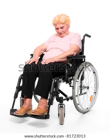 Tired elderly paraplegic woman sitting in a wheelchair on a white. - stock photo