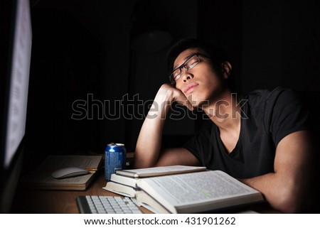 Tired exhausted asian young man studying and sleeping in front of computer in nighttime - stock photo
