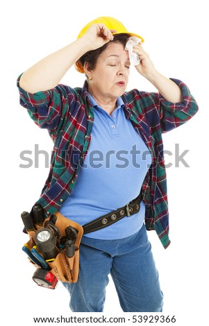 Tired female construction worker wipes sweat from her forehead. - stock photo