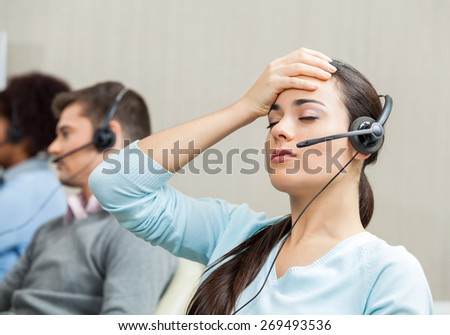 Tired female customer service agent with colleagues in background at call center - stock photo