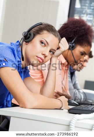 Tired female customer service representative looking away while colleagues working in office - stock photo