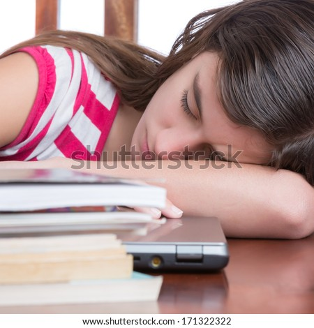 Tired female student sleeping over her laptop with a stack of books on the table - stock photo