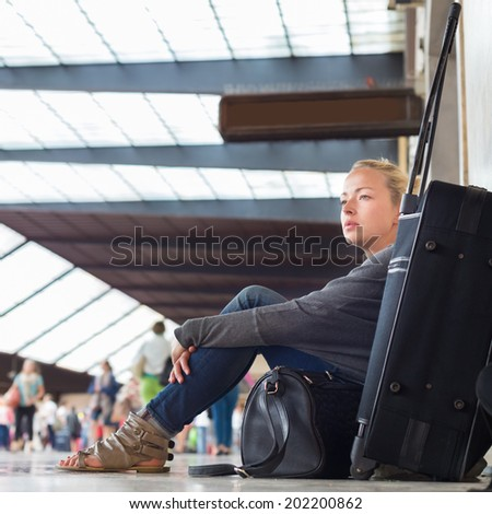 Tired female traveler waiting for departure, sitting on the station floor with all her luggage. - stock photo