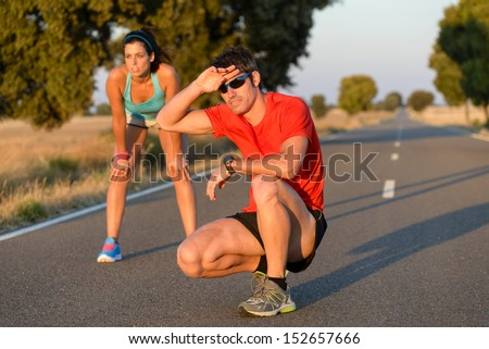 Tired fitness couple of runners sweating and taking a rest during marathon training in country road. Sweaty athletes after running hard. - stock photo