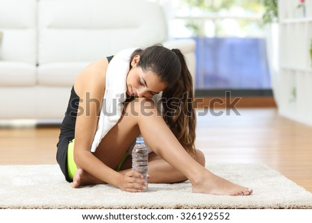 Tired fitness woman resting and thinking sitting on the floor after sport at home - stock photo