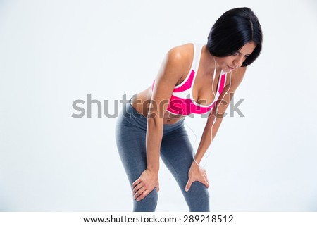 Tired fitness woman resting over gray background - stock photo