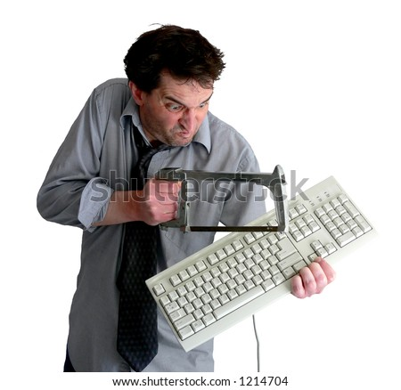 Tired, freaked-out business man sawing a keyboard in half with a hacksaw.