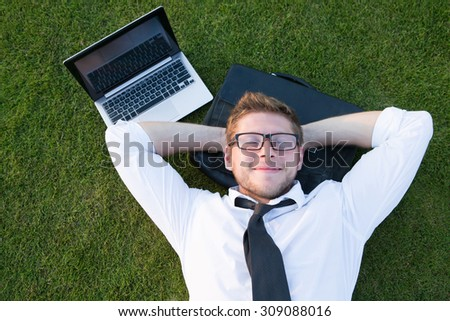 Tired freelancer lying in the park near his laptop computer. Handsome man in glasses resting with his hands on the nape. - stock photo