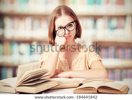 tired funny crazy  girl student with glasses reading books in the library - stock photo