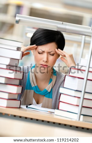 Tired girl with headache sitting at the desk surrounded with piles of books - stock photo
