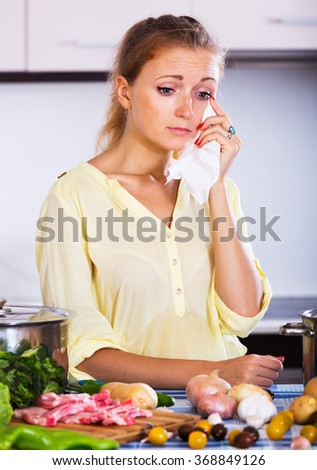 Tired girl with meat and vegetables at kitchen table