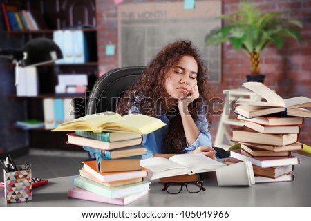 Tired girl with pile of books in office - stock photo