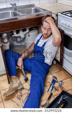 Tired handyman sitting on the kitchen floor