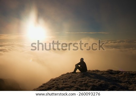 Tired hiker in black sit on frozen grass on hill and watching into misty daybreak. Autumn misty day in mountains.