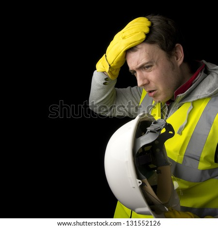 tired, hot, stressed worker removing hat, isolated on black background - stock photo