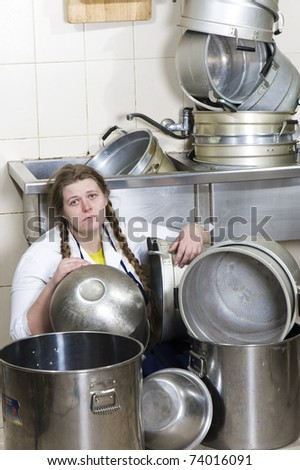 Tired housewife and pile of dirty dishes - stock photo