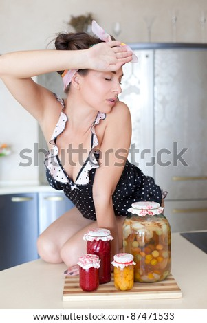 Tired housewife with fruit preserves - stock photo