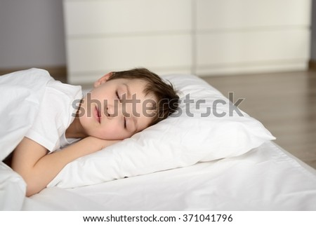 Tired kid sleeping in bed, happy bedtime in white bedroom. Sleeping boy. Sleeping child - stock photo