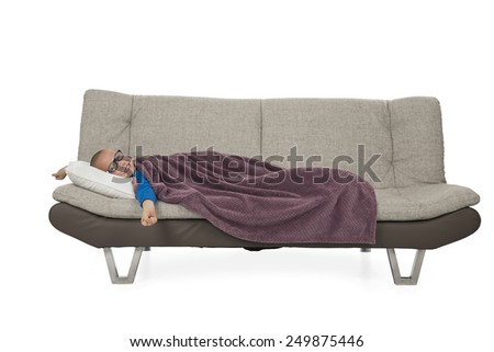 Tired kid waking up from a nice sleep on a sofa against a white background - stock photo