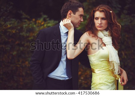 Tired lady touches man's face while he hugs her