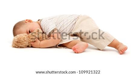 Tired little boy peeking from behind toy bear - stock photo