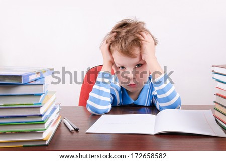 tired little boy sitting at a desk and holding hands to head. boy 5 years. on the desk a lot of books. photo taken on a light background - stock photo