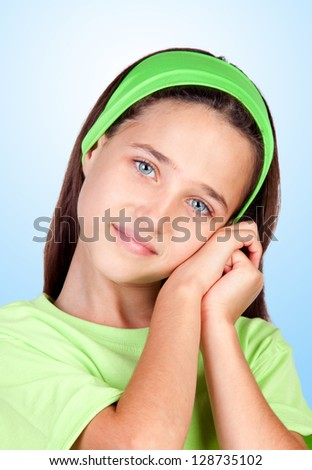 Tired little girl ready to sleep isolated on blue background - stock photo
