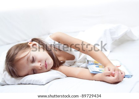 tired little girl sleeping, with hand on book, in the bed - stock photo