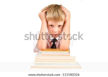 Tired little schoolboy sitting at a table with books isolated on a white background - stock photo