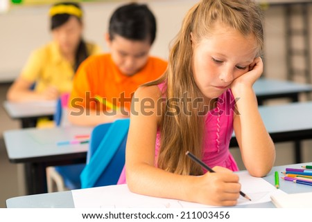 Tired little schoolgirl drawing in classroom - stock photo