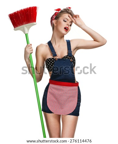 Tired maid standing after spring cleaning with broom / young beautiful American pin-up girl isolated on white background. Cleaning service concept - stock photo
