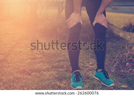 Tired male athlete standing in park at sunset and resting (intentional sun glare and vintage color) - stock photo