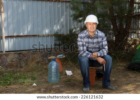 Tired Male Civil Engineer Sitting at the Corner in Construction Site While Looking at Building Progress. - stock photo