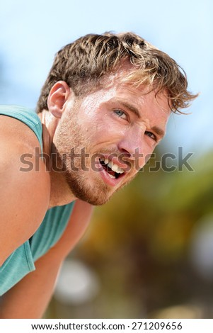 Tired male runner catching breath during marathon training. Running male adult taking a break and breaking a sweat after a run under the sun. Fitness athlete exhausted breathing with difficulty. - stock photo