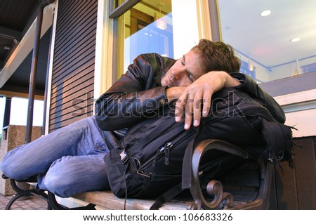 Tired male traveler sleeping on bench at train station