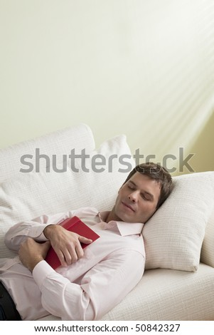 Tired man asleep on the couch - stock photo
