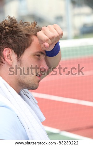 Tired man by tennis court - stock photo
