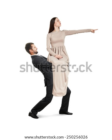 tired man holding his woman and going forward. young woman in long dress sitting on man and pointing at something. isolated on white background - stock photo