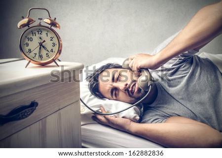 tired man in the bed talking on the phone - stock photo