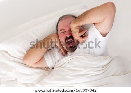 Tired man lying in bed stretching and yawning in an effort to wake up as he debates just turning over and going back to sleep in the morning - stock photo