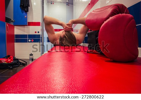 Tired man lying in the locker room after finishing training - stock photo