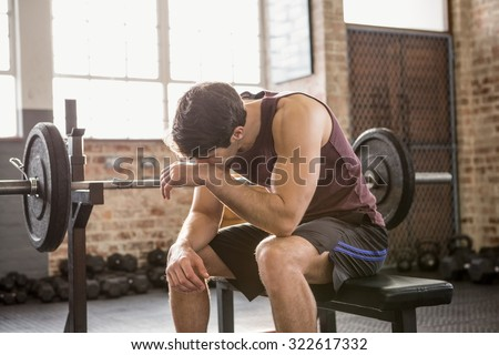 Tired man sitting on the bench at the gym - stock photo