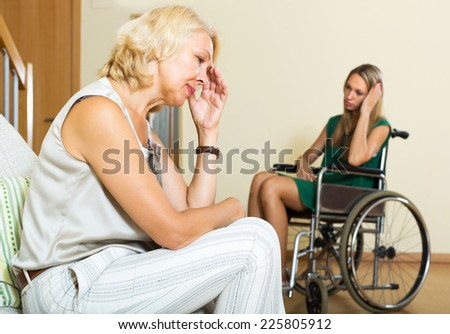 Tired mature female and disabled person on chair indoor - stock photo