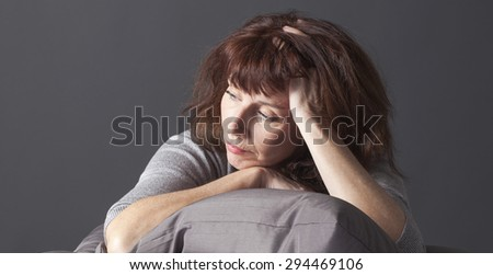 tired mature woman resting her face and hands laying down on cushions for comfort while having health care problems