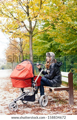 Tired mother sitting on park bench with baby in stroller - stock photo