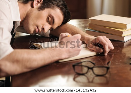 Tired of overworking. Handsome young author sleeping at the table with a pen in his hand - stock photo