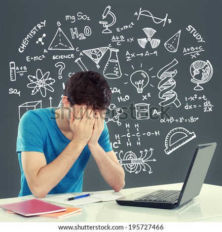 Tired of studying. young man covering his head while sitting. gesture of depression - stock photo