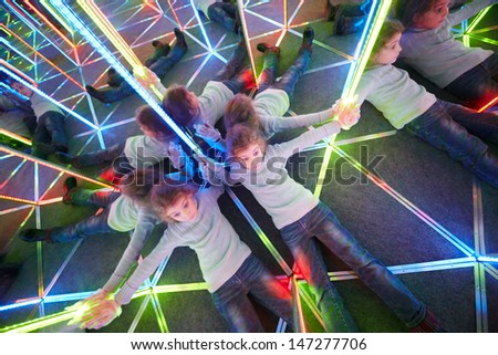 Tired of wandering little girl lies on floor in mirror maze - stock photo