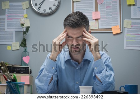 Tired office worker at desk with headache touching his temples.