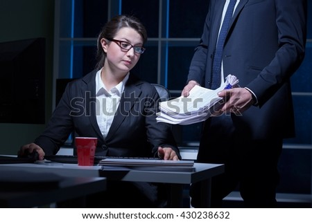 Tired office worker sitting beside desk doing paperwork, working at night - stock photo